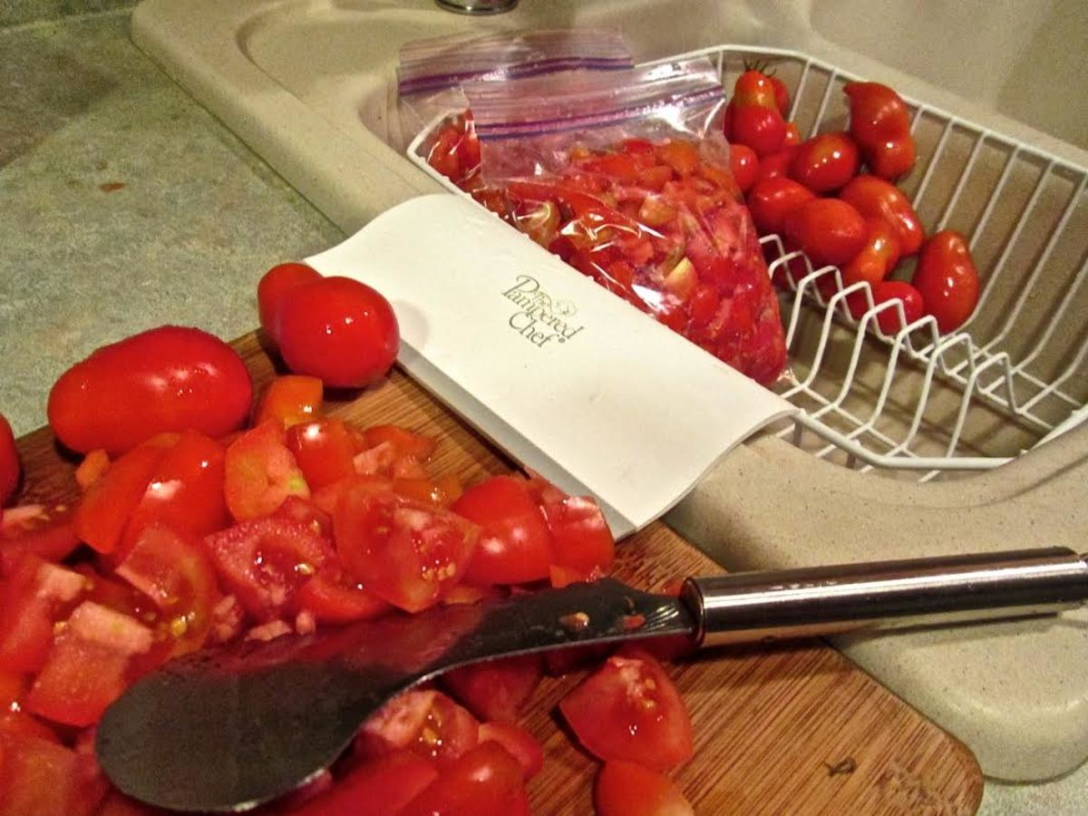 Putting sliced tomatoes into freezer bags.