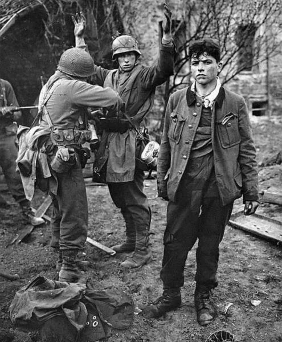 U S soldier frisks German for hidden weapons, another dishevelled POW stands nearside looking sorry for himself - these are just about school leaving age, (older than some who 'defended' Berlin against the Russians)