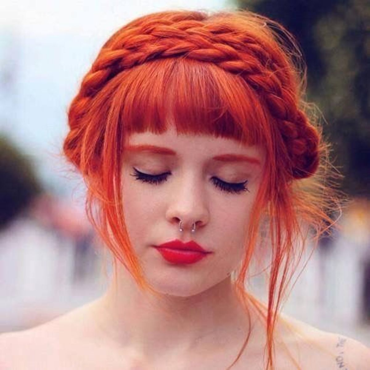 most innocent hairdo style with a braid on top of the head like a hair band and straight bangs. Stunning orange red hair
