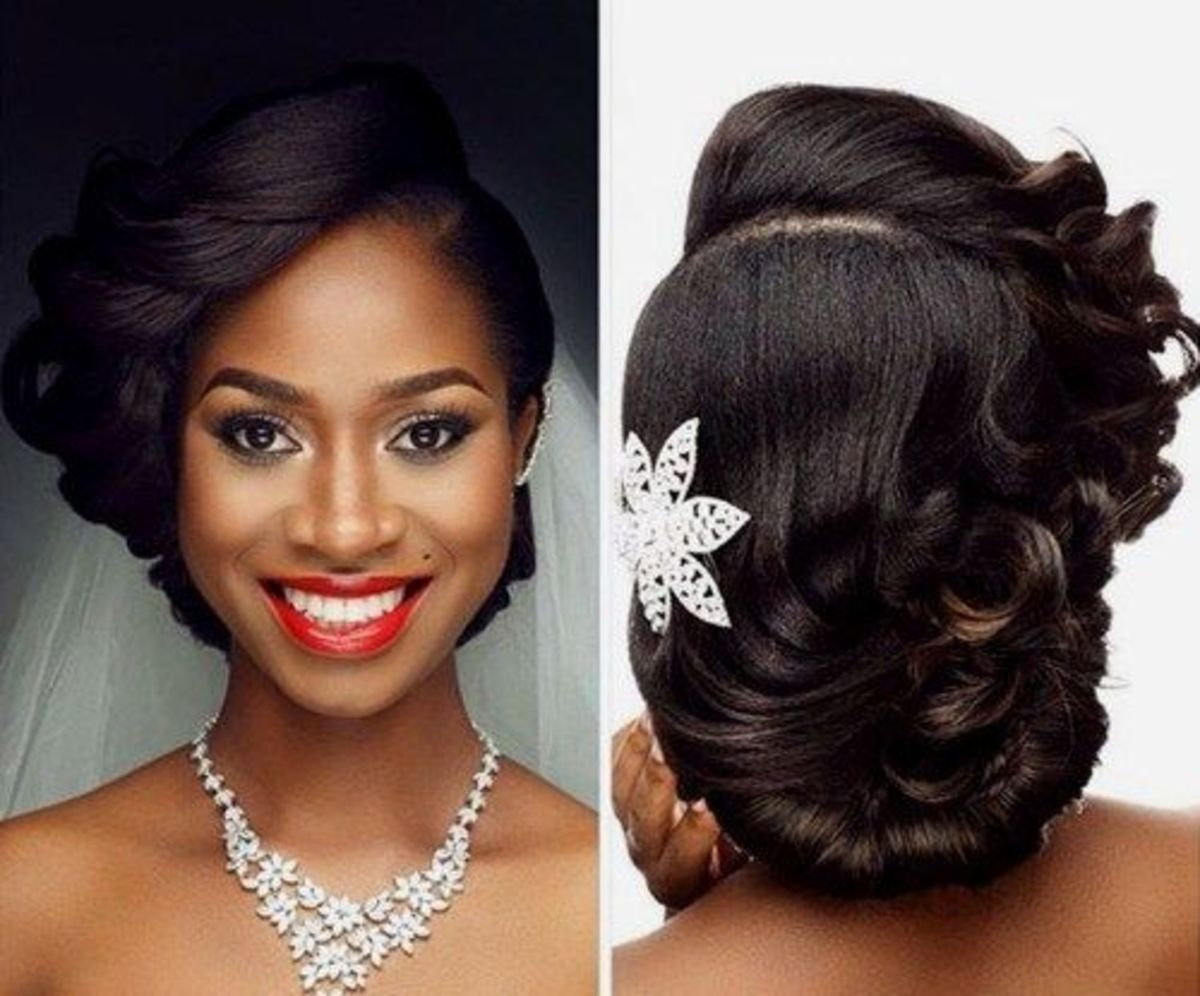 beautiful black woman with low hanging hair bun with stone encrusted flower jewellery