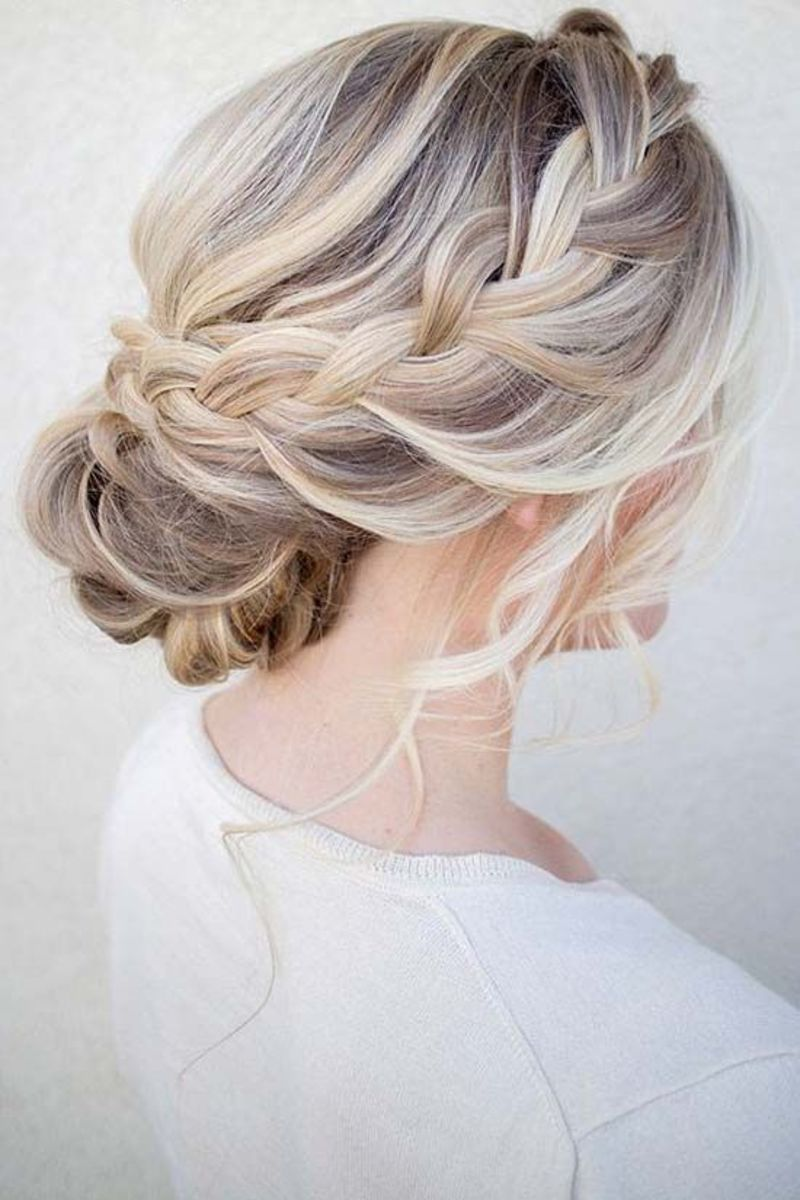 Silver blonde hair chignon or bun with a single braid styling one side of the head