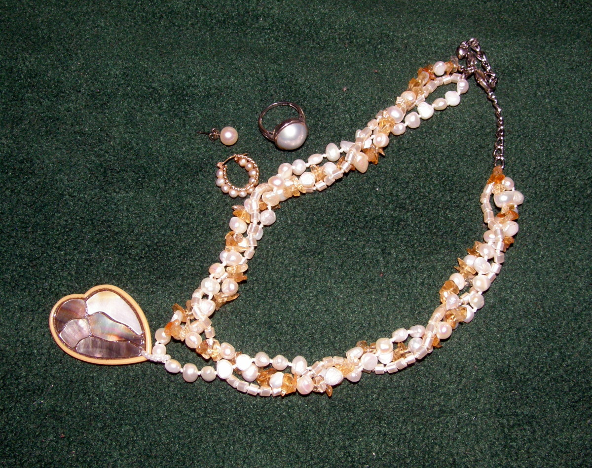 White pearls and citrine necklace.  Beside it are a pearl stud, a pearl hoop earring, as well as a Mabe pearl ring.