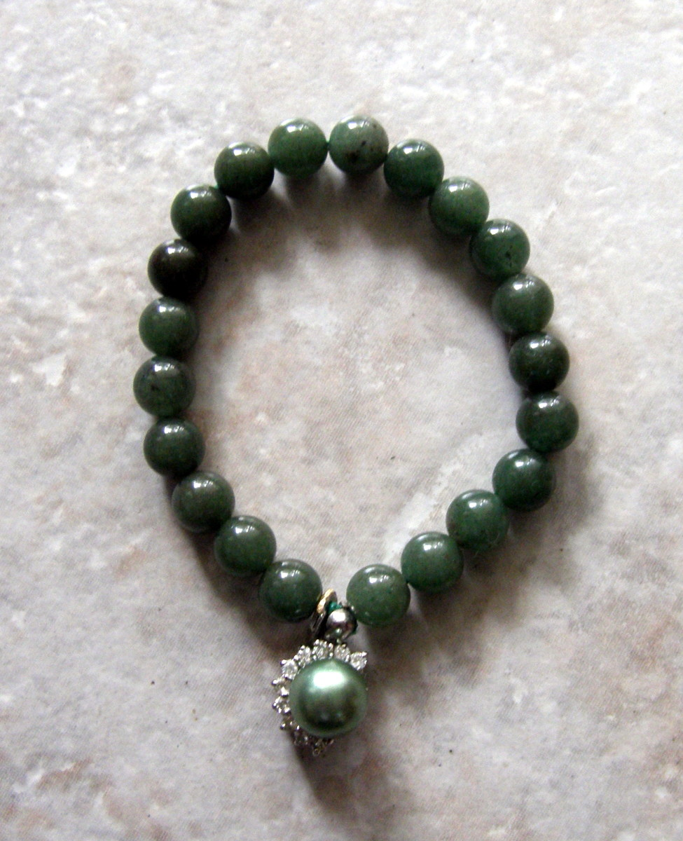 Jade bracelet with enhanced green pearl, surrounded by cubic zirconias.   Many cultures, including the Irish, see the color green as a symbol of good luck.