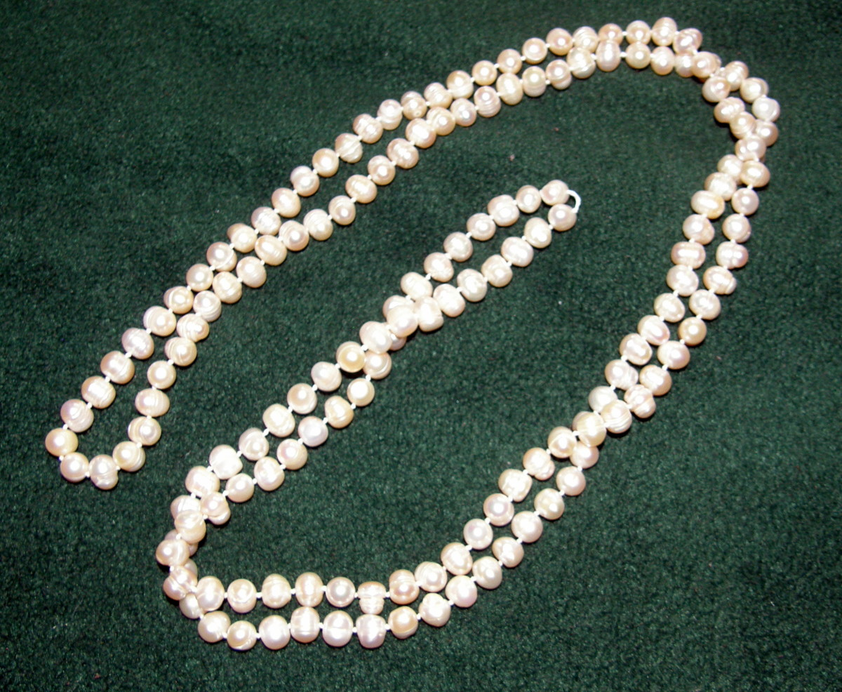 Rope necklace of cream pearls each pearl measuring roughly 11-12 mm...total length of 4 feet