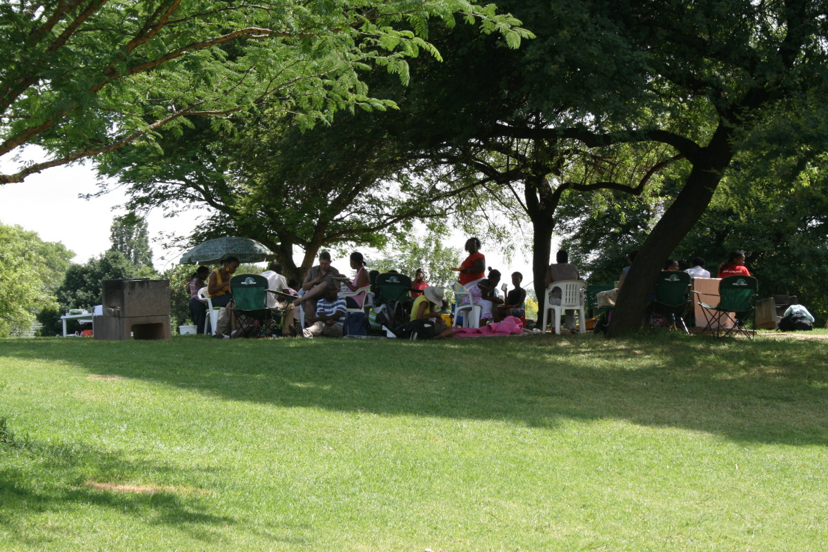 "A group enjoying a ""braai"" under the trees"