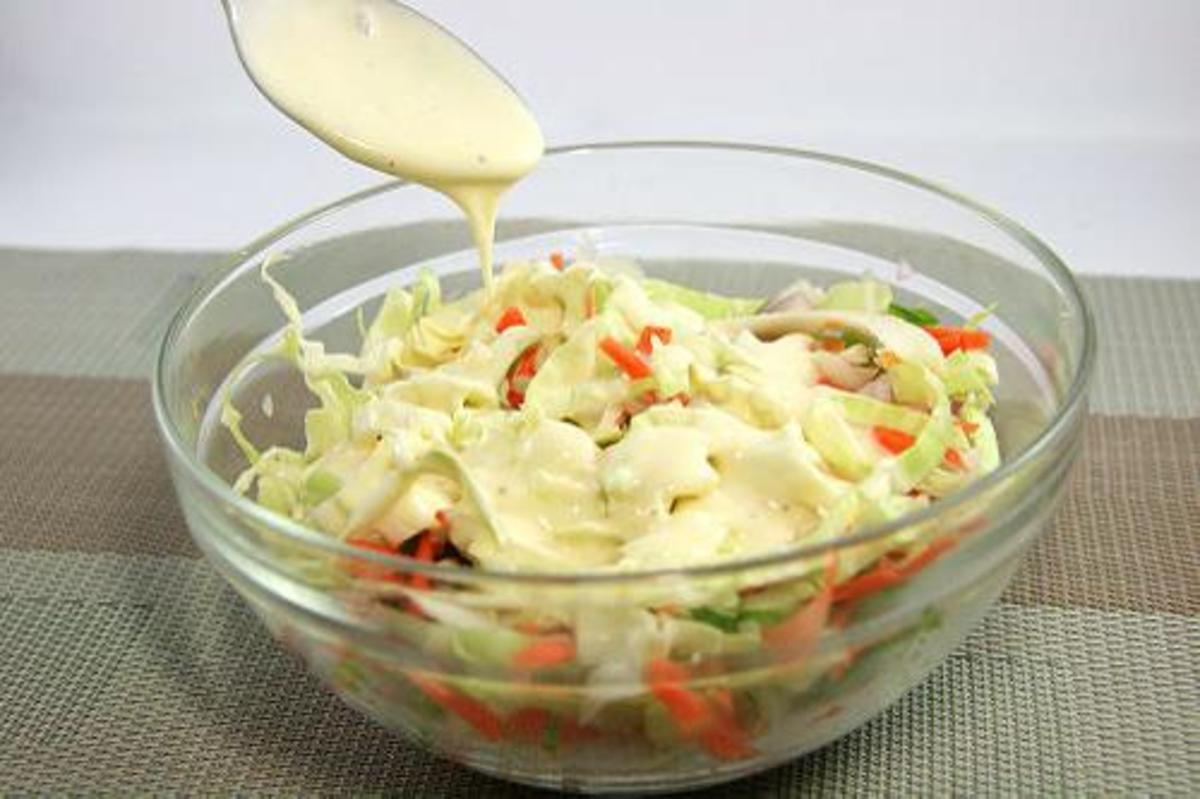 Use a large spoon and mix your cole slaw dressing into the slaw, carrots, peppers and onions and stir well.