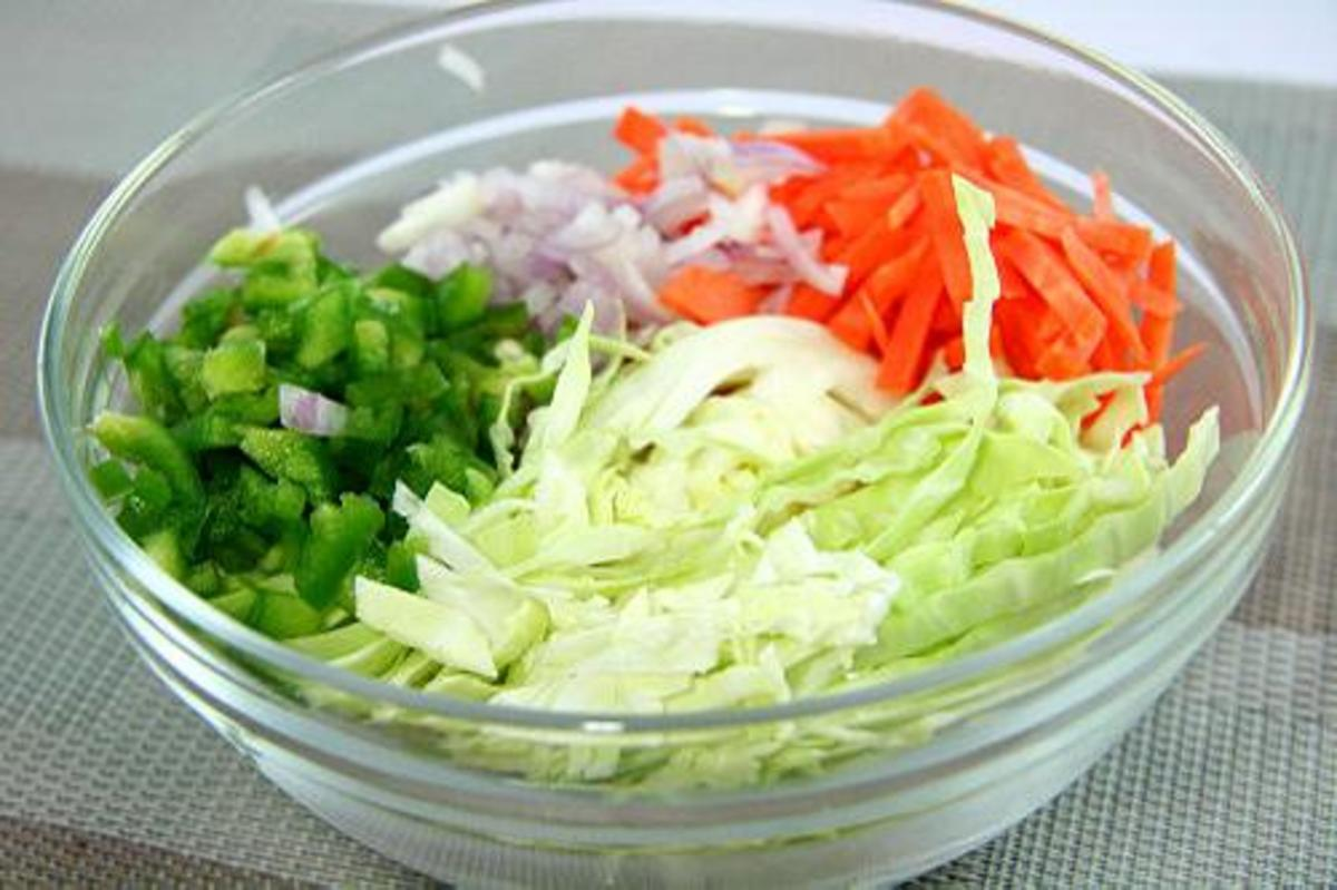 You'll want to combine your carrots, green bell peppers, onions, and cabbage in a large bowl.
