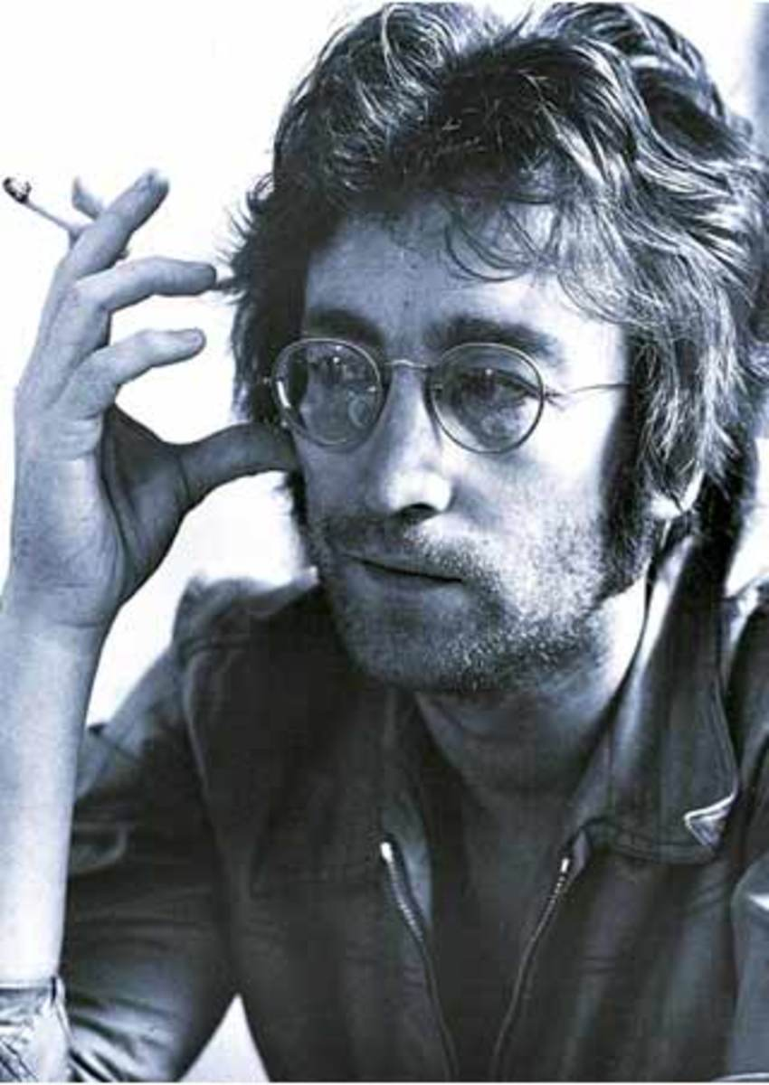 John Lennon Pilgrim of Peace - black and white photo with cigarette in hand and wearing his iconic glasses