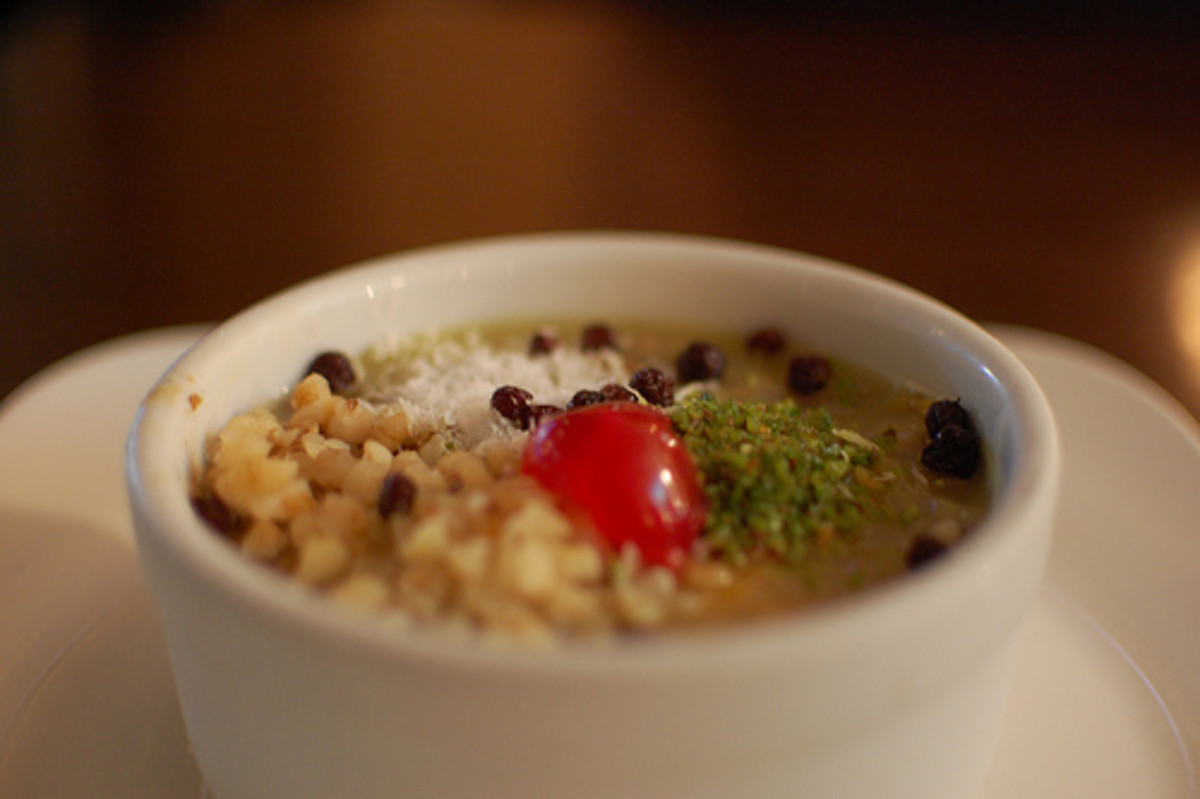 A small bowl of asure topped with grated pistachios, nuts, raisins & other currants.