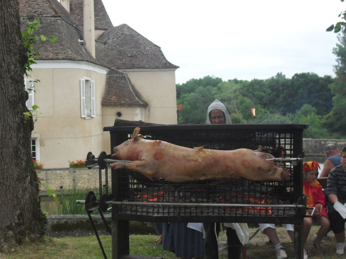 Roasting a pig  at a medieval party on Le Pechereau- France