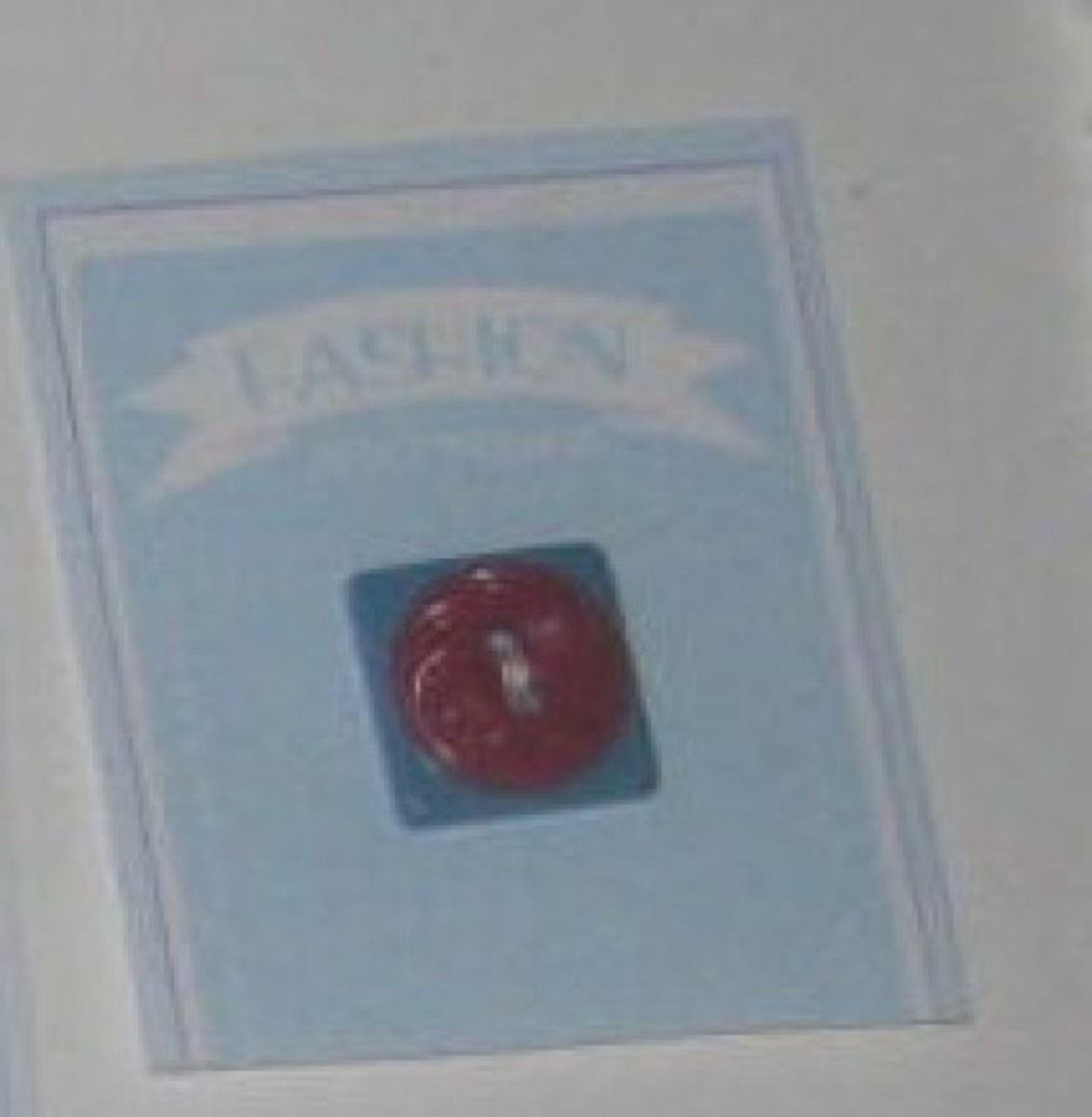 Two vintage buttons layered and displayed on button card.