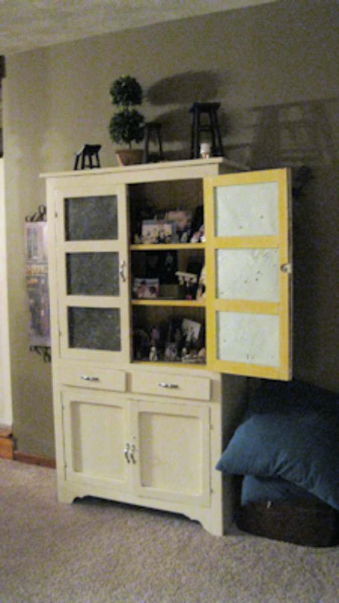 Another cabinet in the living room. It's a large pie safe. One of the doors remains open and displays family photos. Throws and afghans are stored in the bottom.