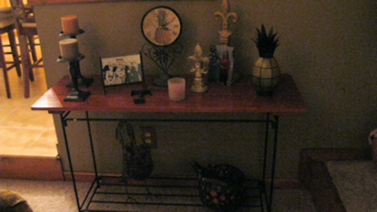The sofa table sits on a wall in the living room and is filled with a nice mixture of old and new -- cast iron tea kettle and wire chicken on the bottom shelf with frames, candles and figurines on the top of the plank board surface.