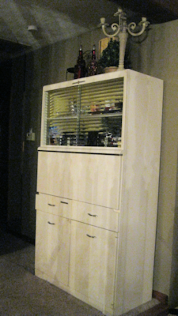 This is an original Hoosier Cabinet that sits in the hallway. Notice the new candelabra and red bottles on top. My sister stores seasonal décor in the pull out counter area. Easy to get to but not seen in the mean time.