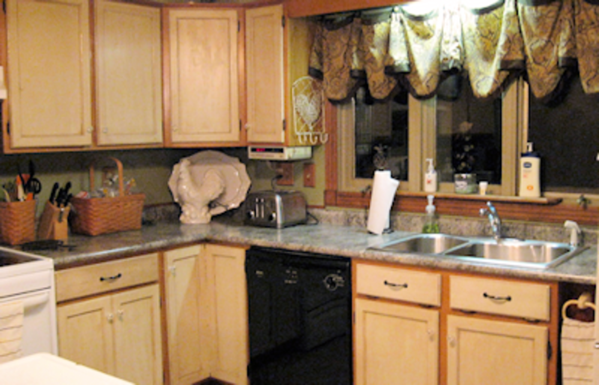 She re-did the cabinets in the kitchen with a two-tone look -- very retro -- then added granite-look formica counters. Mixing old and new again. See the large ceramic rooster sits next to some new Longaberger baskets.