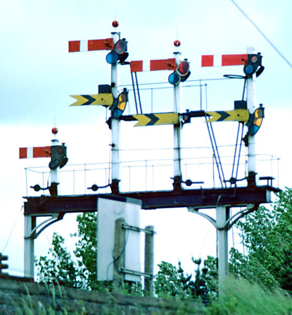 A short gantry of semi-distant semaphore signals for one direction of travel, i.e., home signal above distant