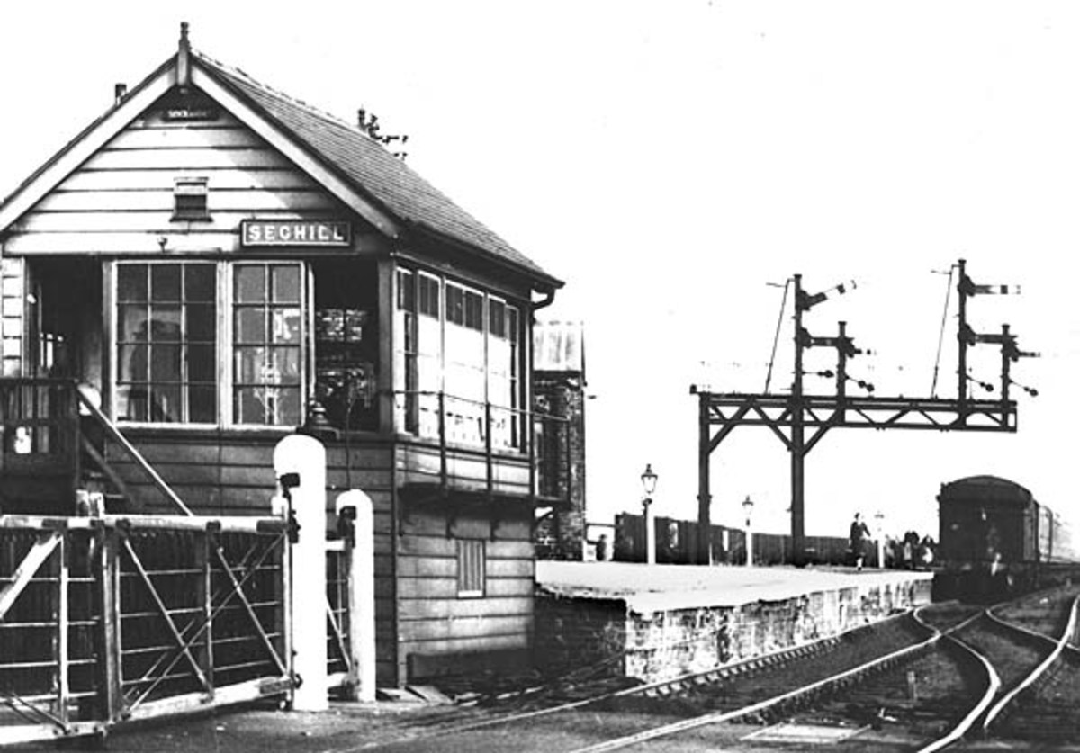 Seghill Station signal cabin controls the crossing gates as well as the signals - interesting bracket formation at the far end of the platform
