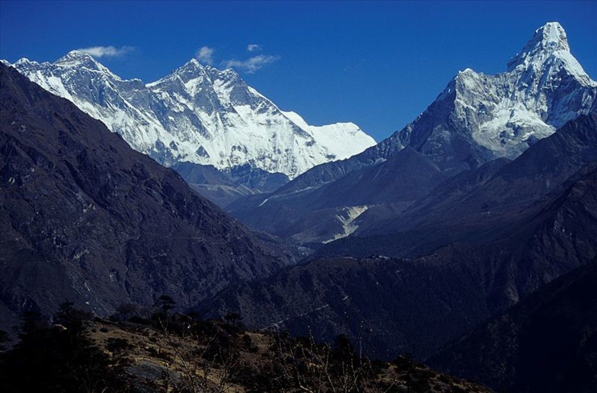 Mount Everest (in the clouds) and the peak of Ama Dablam (to the right.)