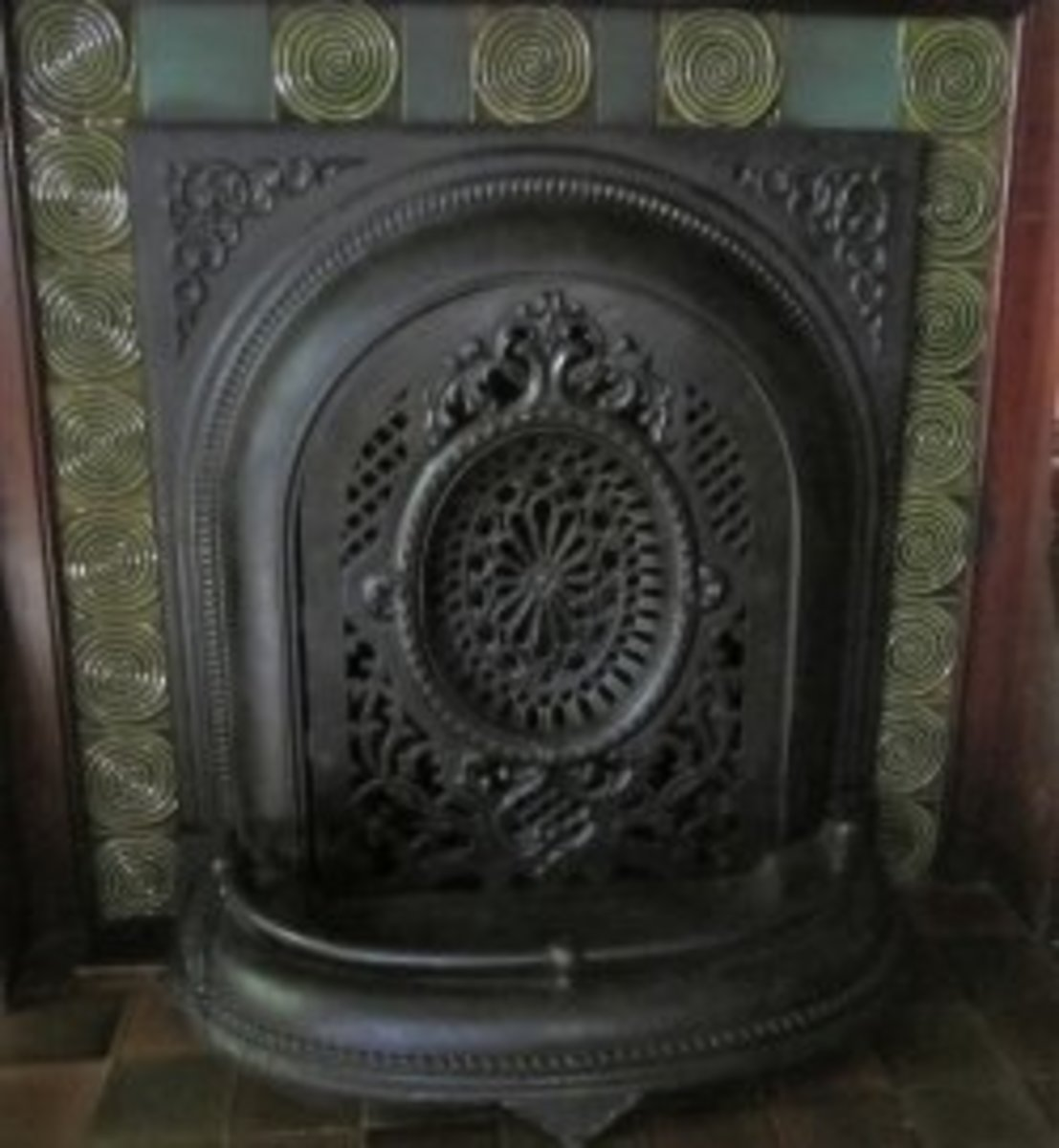 Coal burning fireplace with cast iron grille in front. © 2012-15 Restoration Fabrics & Trims LLC/Old House Interiors