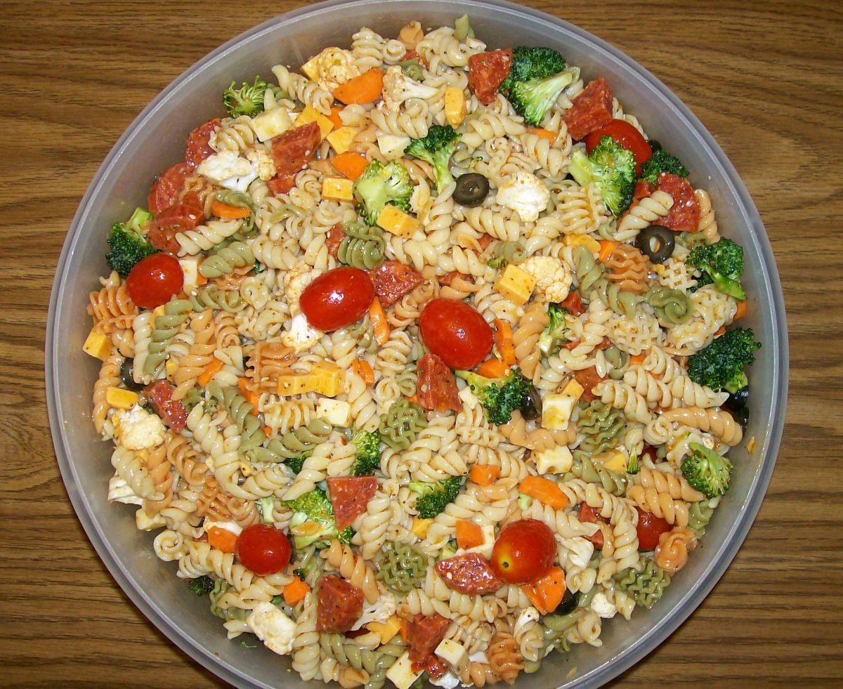"""I mixed everything in a large Tupperware """"That's a Bowl"""" and then transferred the final Supreme Pasta Salad to a pretty, green glass bowl."""