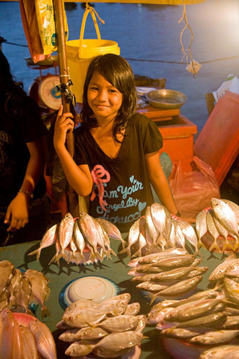 Girl selling fish at Filipino market