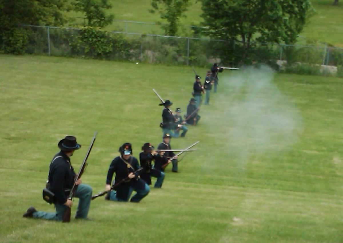 Living Historians Load and Fire during a reenactment. The soldier, second from left, is about to load his musket from the Kneeling Stance. His musket was brought back on his right side, rammer-side up, and in this position he will load the firearm
