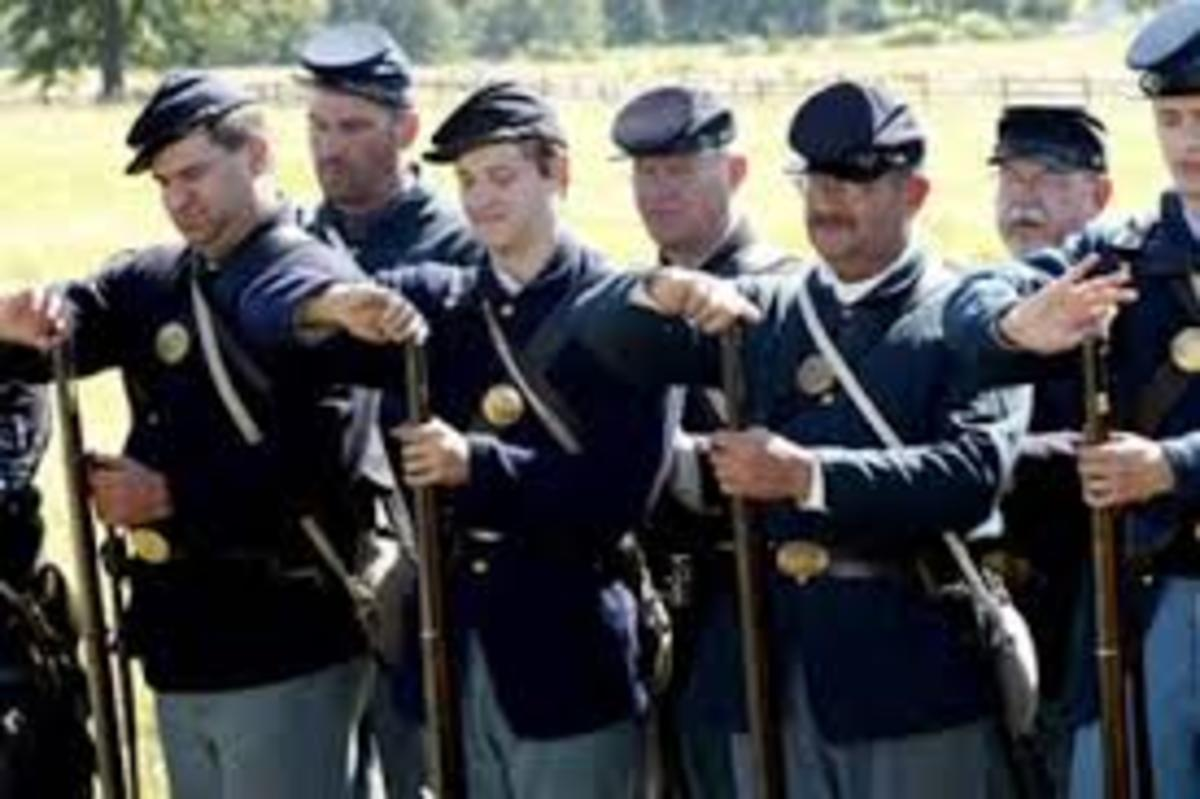 """Members of the 20th Maine Volunteers Living History Association """"Charge Cartridges"""" (place the cartridges, powder-side down, into the muzzles of the muskets)"""