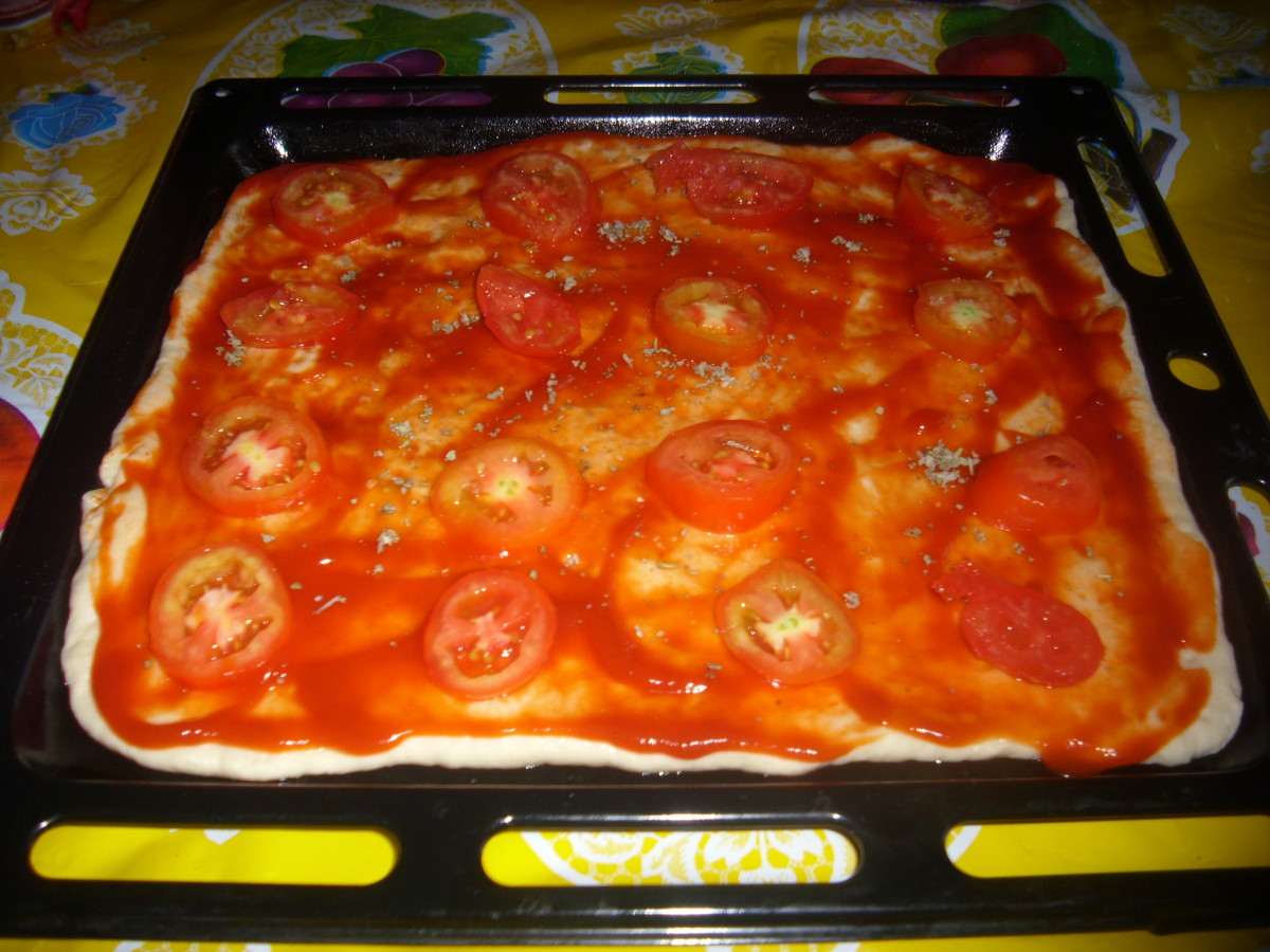 The dough spread with tomato sauce, salt, white pepper, dried oregano, dried basil and topped with round sliced tomatoes.