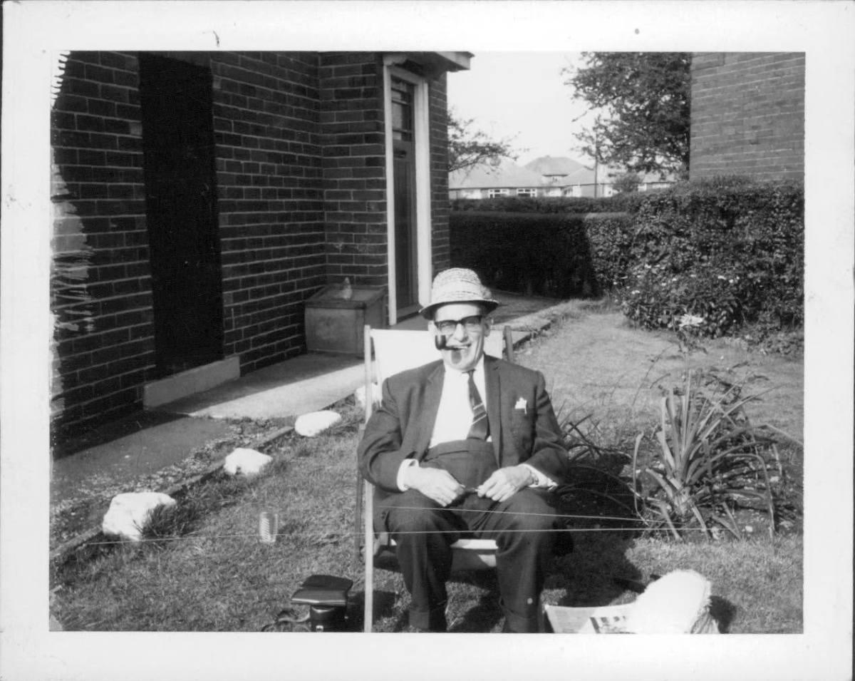 Grandad sitting in his deckchair, wearing a sun hat.