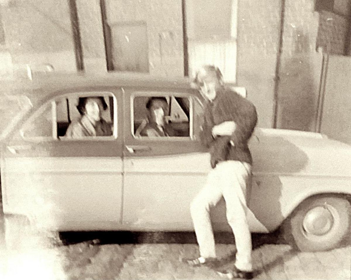My brother Eric leaning on grandad's car, with grandad driving and mum in the back seat.