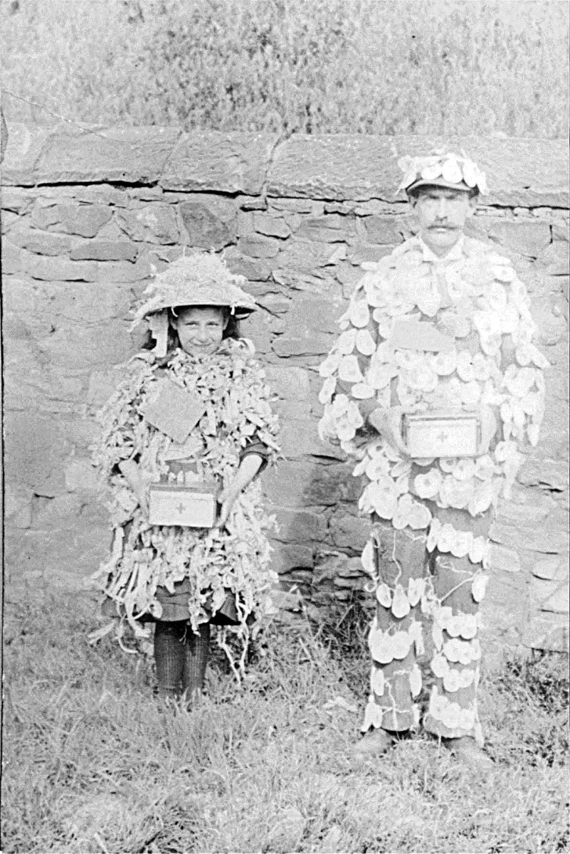 Grandad's father with daughter Annie Triggs - in fancy dress.Looking at the costumes, Great Grandad Triggs' suit is covered in poppies and their boxes have a red cross on them, so it may be WWI related.