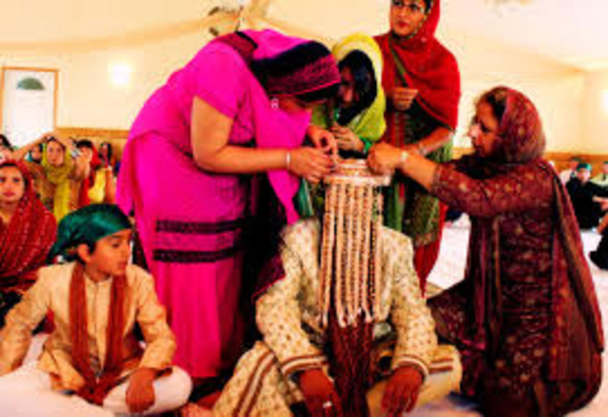 The groom being dressed up for the marriage ceremony