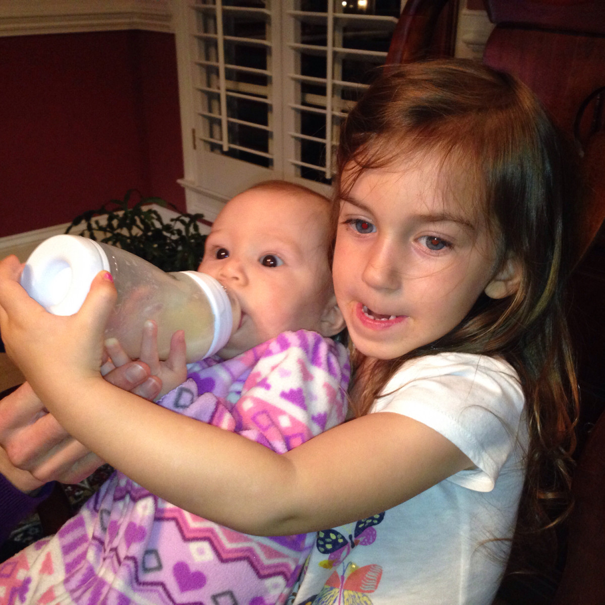 My Granddaughters . See her cousin feeding her with no problems