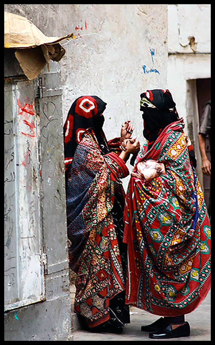 Two Yemeni females in Sana'a city while wearing the Sana'ani Sitarah with its Mughmug and Lithmah