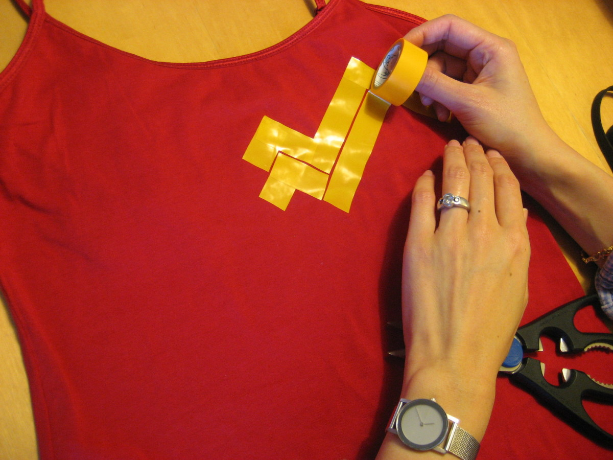 Create your own Wonder Woman symbol on a red shirt with yellow tape.