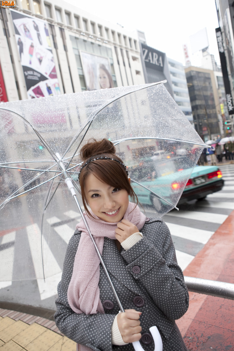 Azusa Yamamoto is standing in the rain and still smiling in spite of the overcast conditions.