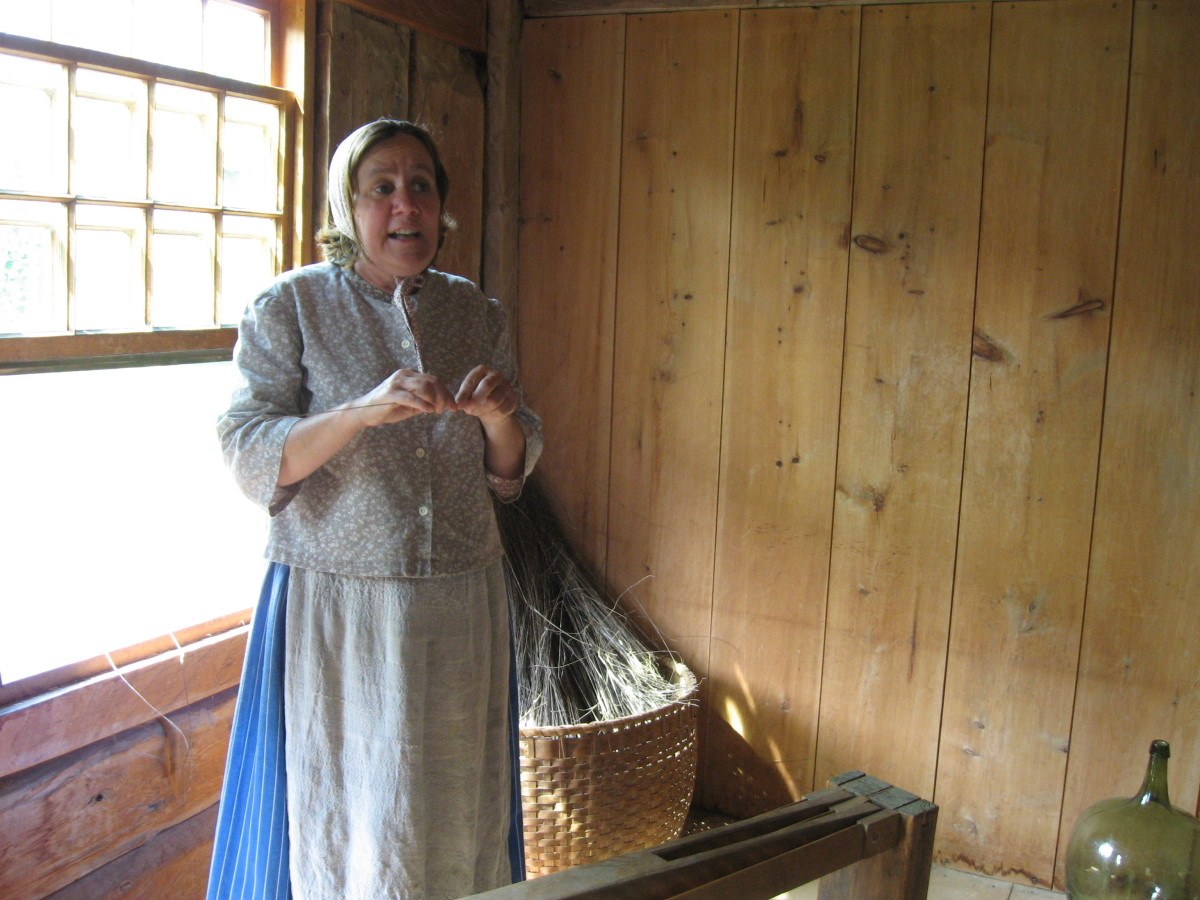 The same docent explains to visitors how they make the fabric. In the basket behind her, you see the flax waiting to be made into fiber for weaving.