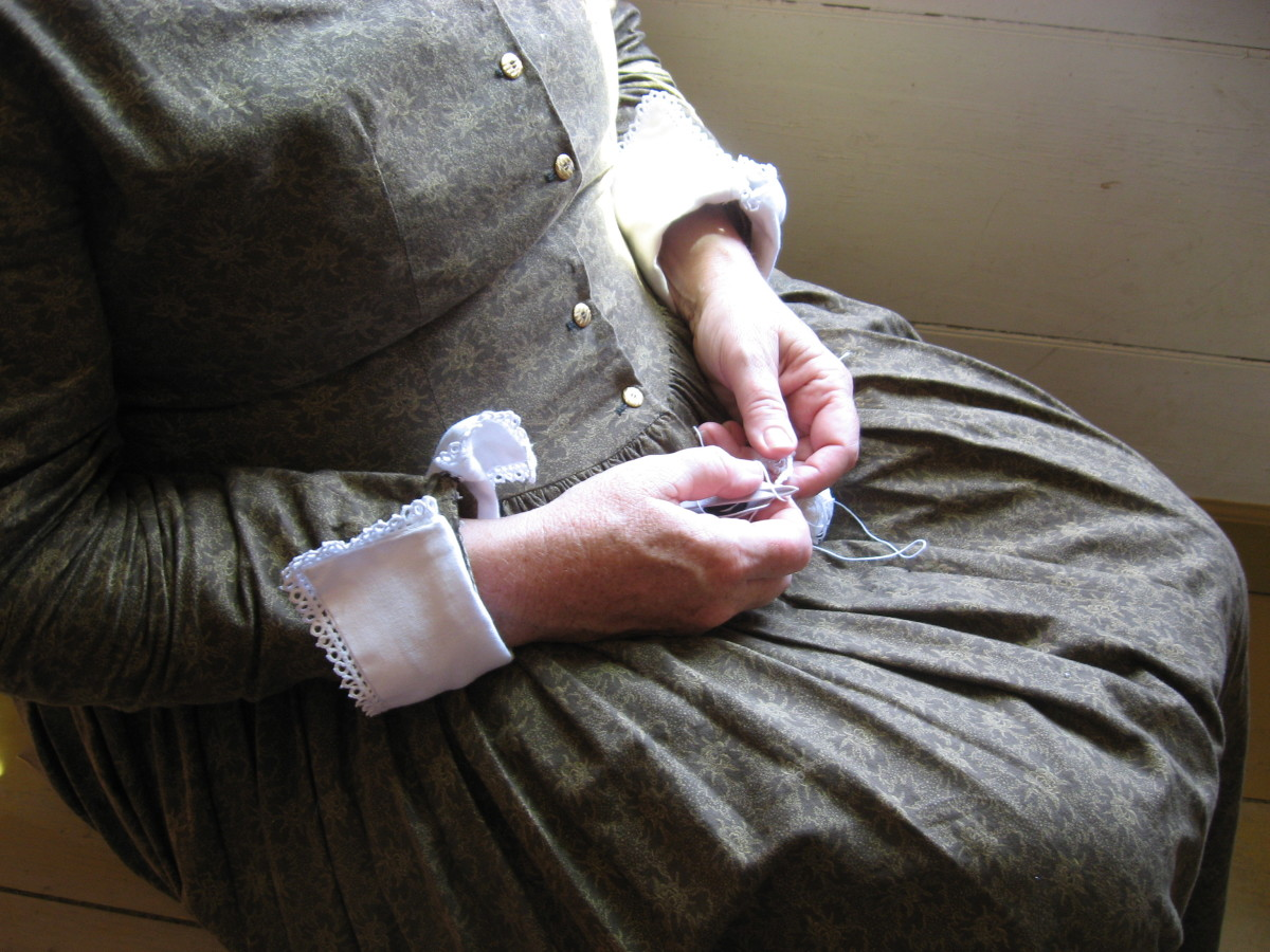 Here's a woman is making lace. You can see examples of it on the cuffs of her dress. This dress appears more formal than that worn by women in the more humble homes. The dress fabric is probably store-bought.
