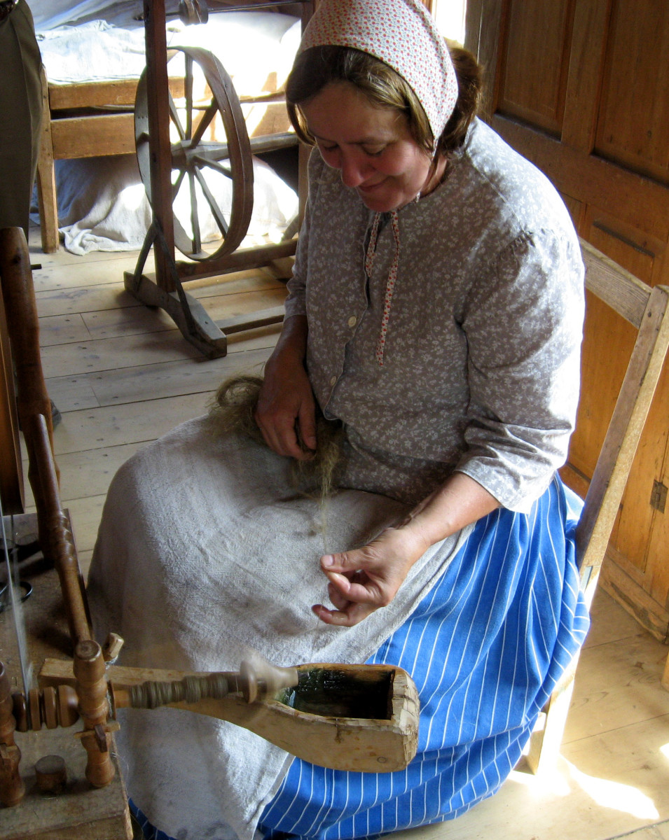 Stripes seem to be popular for the gathered, long skirts. This woman wear a patterned cap that ties under her chin, instead of the plain white head covering. Her apron is a rough weave, so possibly flax or linen. She is spinning fiber.