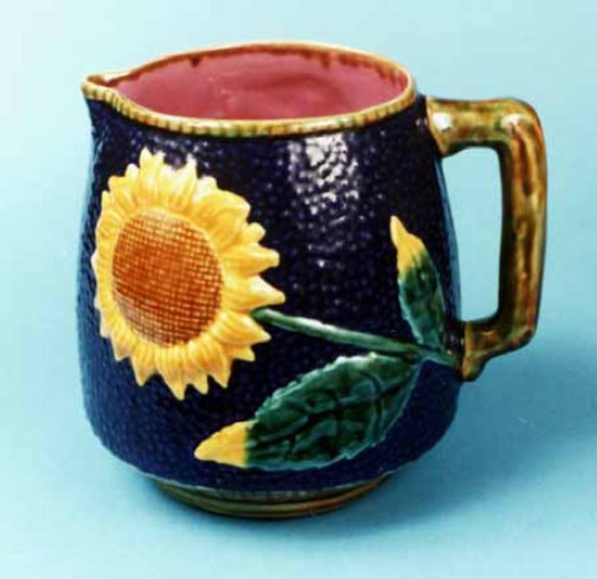 The photo depicts a Sunflower pattern pitcher. The mold for this  pitcher   was taken directly from an old original.Majolica pitcher. The mark of the original pitcher's maker can, Etruscan Majolica, appears on the bottom of this reproduction.