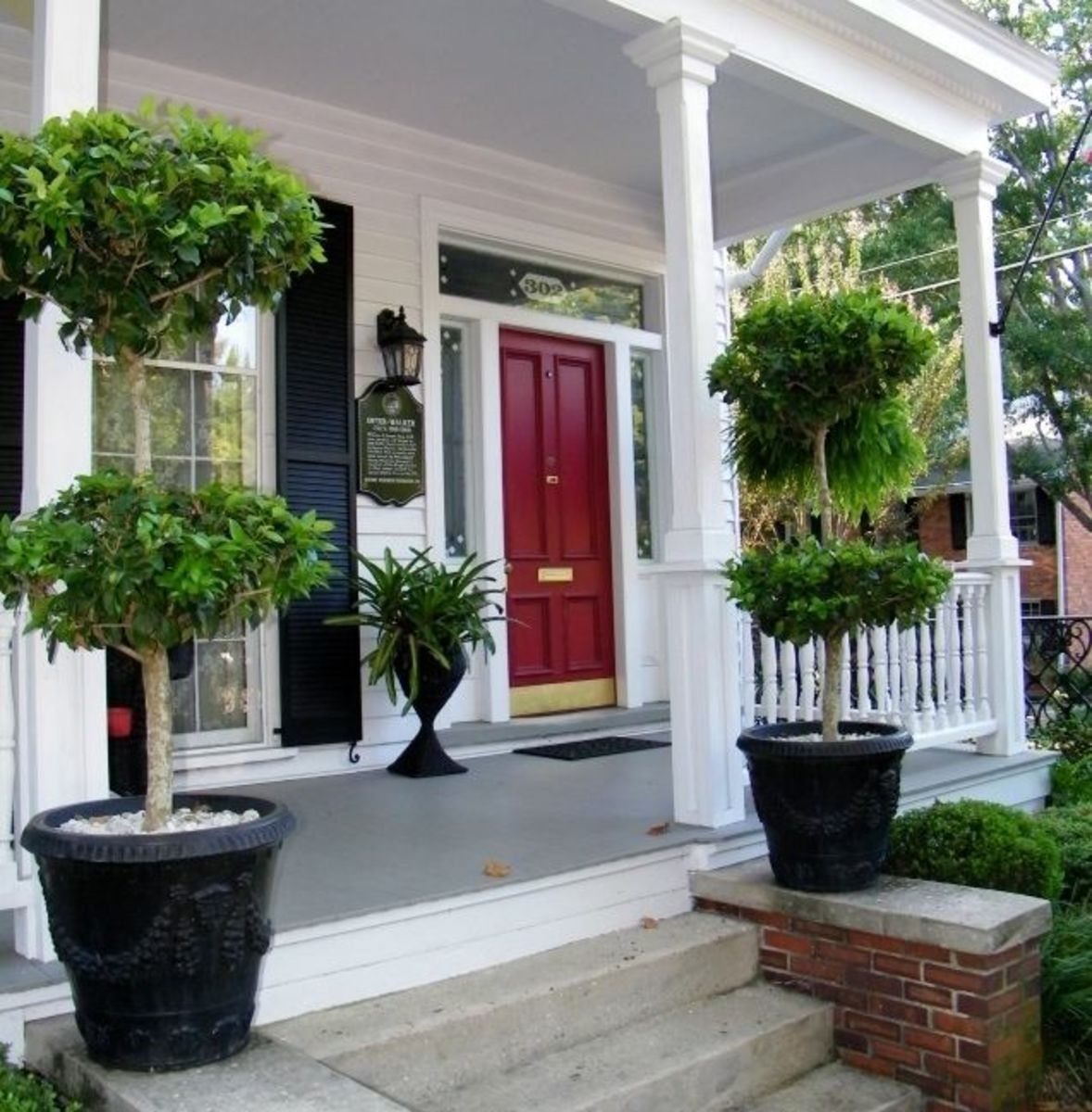 Topiaries flank a bright red door