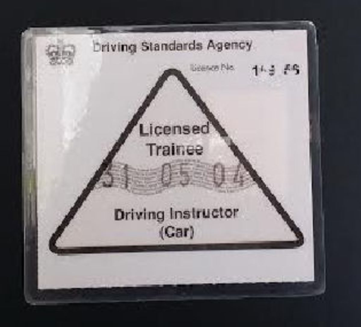 Trainee Potential Driving Instructors (PDIs) display a pink triangular badge