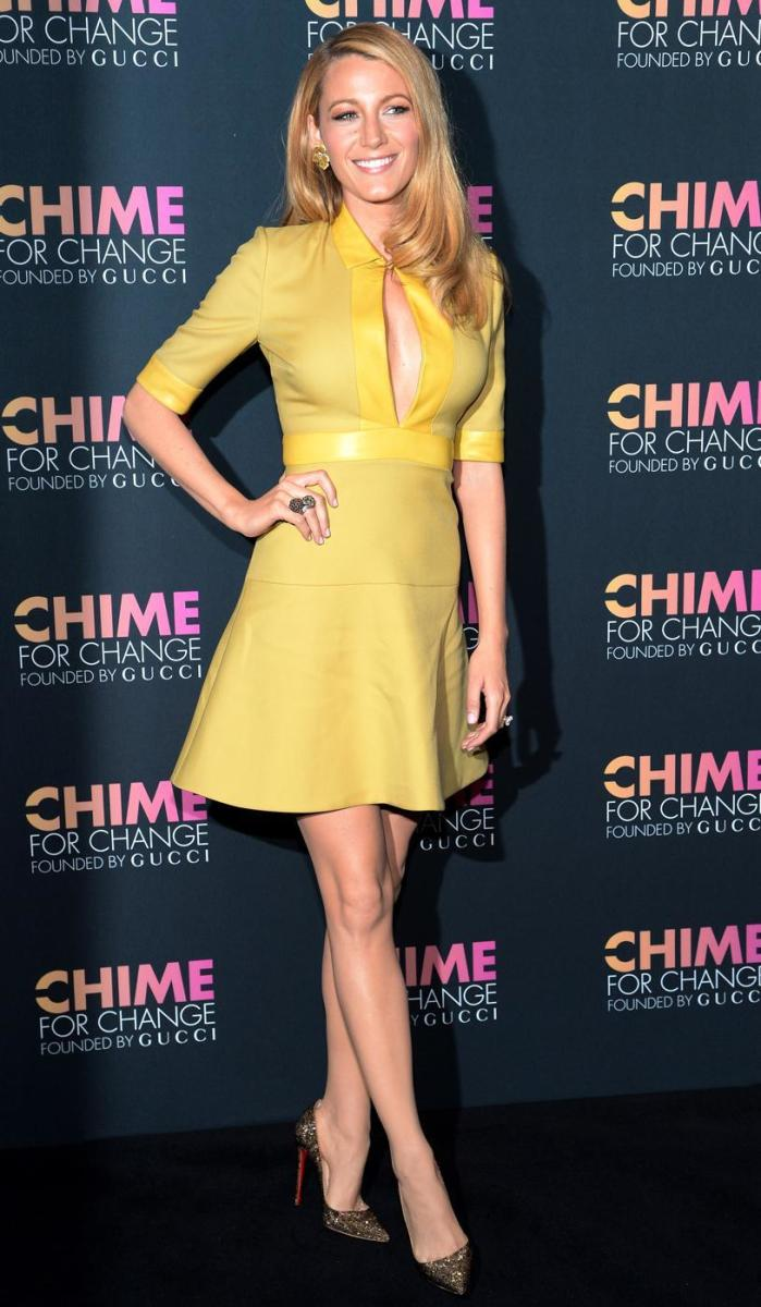 Blake Lively showing off her cleavage and legs in a short yellow keyhole dress and high heel