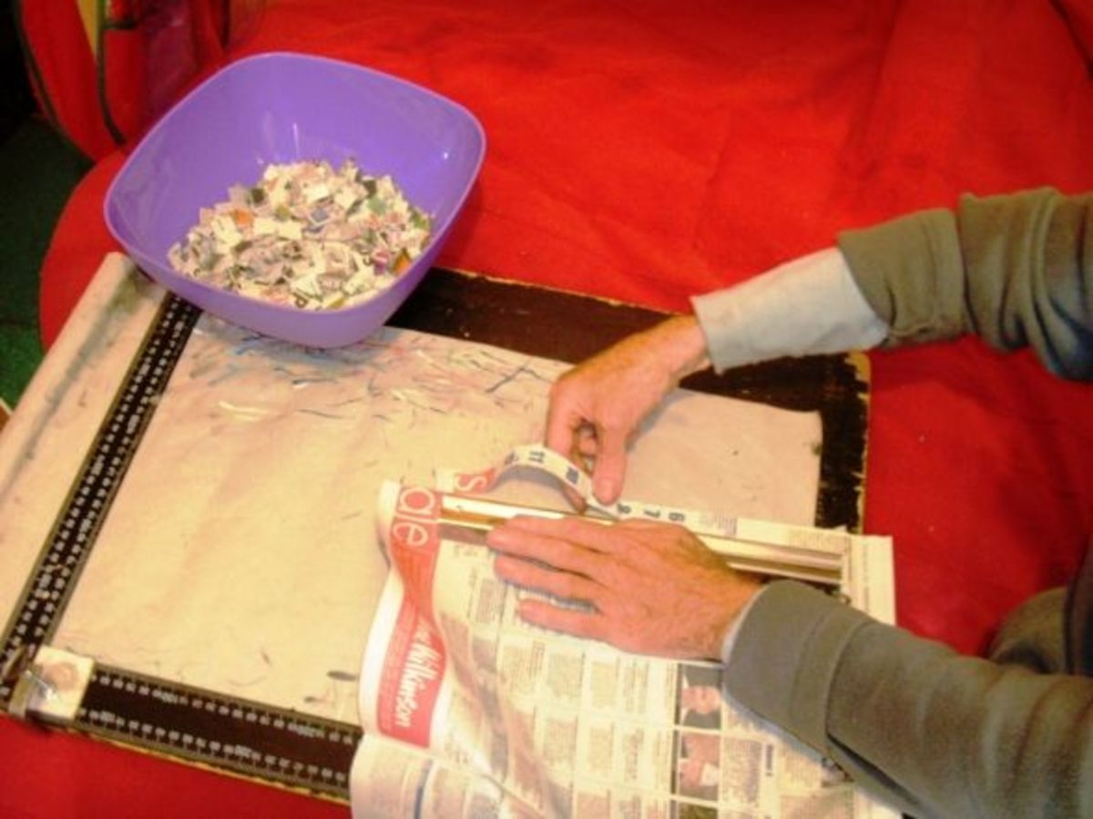 Tearing the newspaper into long strips along the edges where it is plain.