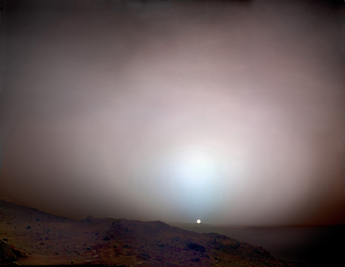 Sunset on Mars. Appearing only about two-thirds the size it does from Earth, the Sun sets behind the 50-mile-distant rim of Gusev Crater. The blue glow is caused by light-scattering dust suspended in the atmosphere. Mosaic composite photograph. Taken