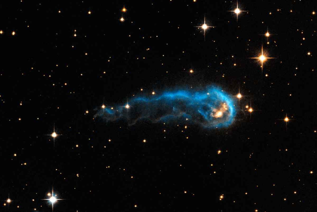 "This light-year-long knot of interstellar gas and dust resembles a massive caterpillar. Harsh winds from extremely bright stars are blasting ultraviolet radiation at this ""wanna-be"" star and sculpting the gas and dust into its long shape. The culprit"