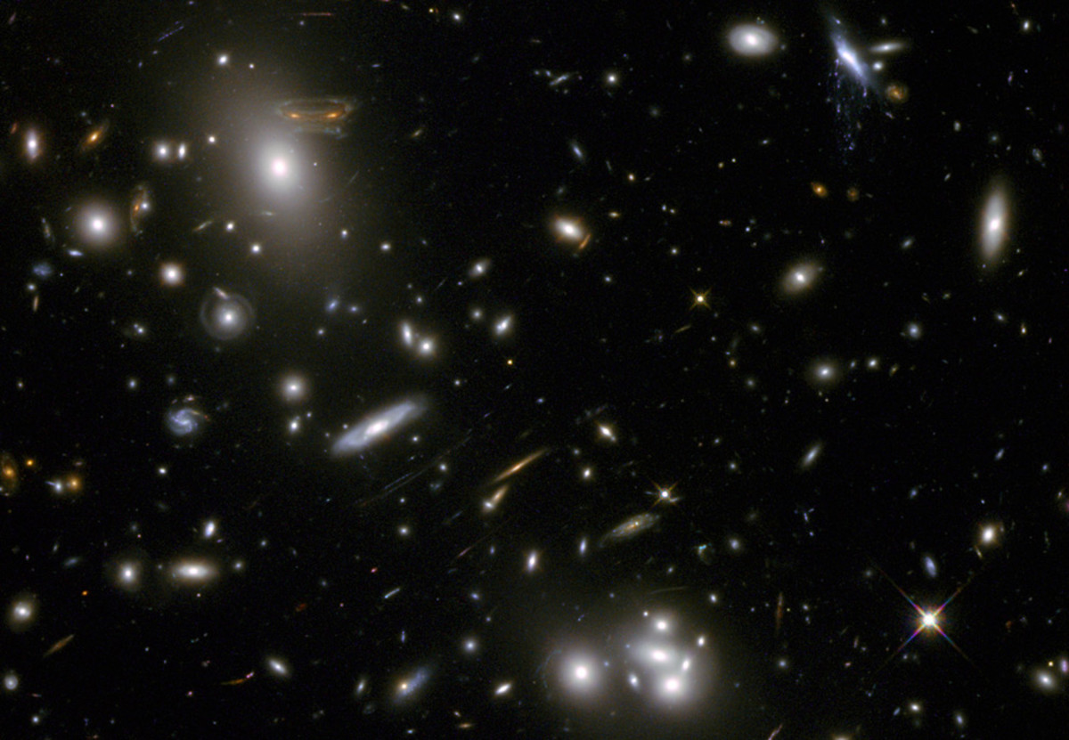 The gravitational field surrounding this massive cluster of galaxies, Abell 68, acts as a natural lens in space to brighten and magnify the light coming from very distant background galaxies. Like a funhouse mirror, lensing creates a fantasy landscap