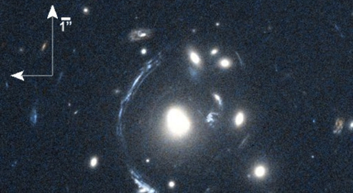 Smeared and Magnified Galaxy The young galaxy SDSS090122.37+181432.3, also known as S0901, is seen here as the bright arc to the left of the central bright galaxy. The distorted view of S0901 is caused by gravitational lensing, resulting from one or