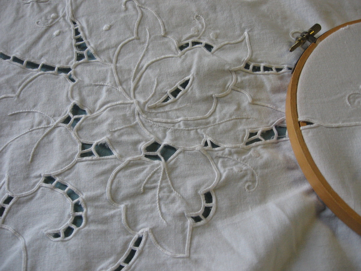 the table cloth is divid up into sections with the more intricate pattern being in the center