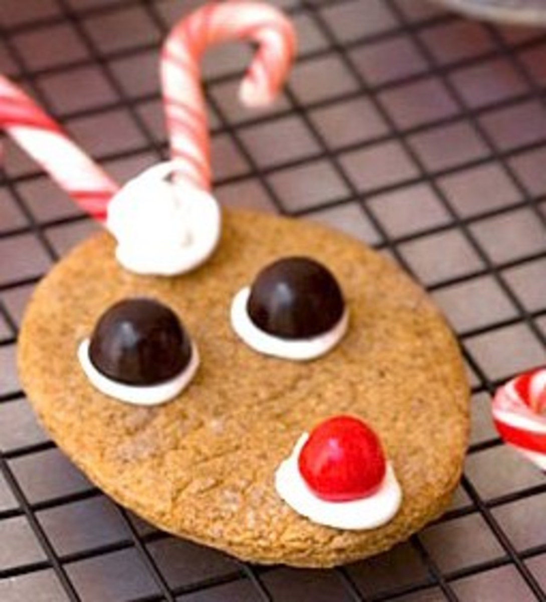 Easy Reindeer cookies made from gingersnap cookies. Icing holds on the chocolate candy eyes, nose and peppermint candy cane antlers.